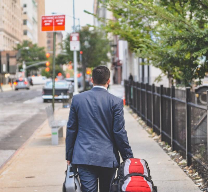 öltönyös férfi bőrönddel távozik
