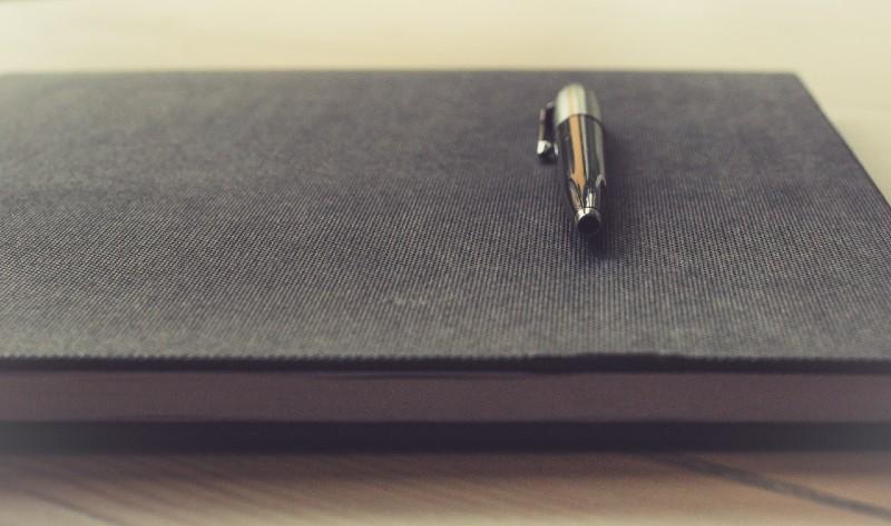toll egy fekete színű jegyzetfüzeten