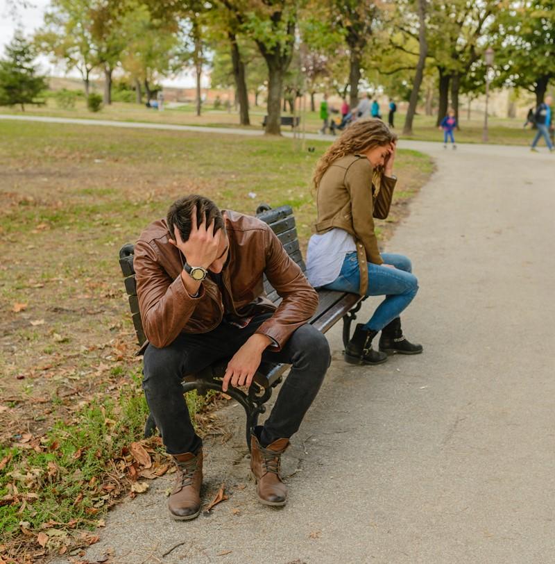 férfi és nő veszekednek padon a parkban